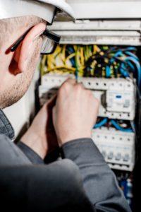 Eletricista trabalhando em disjuntores desarmando